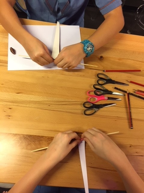 The students are rolling the paper on wooden skewers to achieve a oval or round appearance